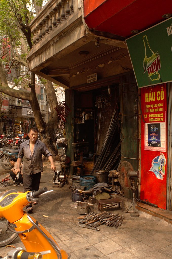 A man working at a sidewalk mechanics shop in Hanoi, Vietnam.